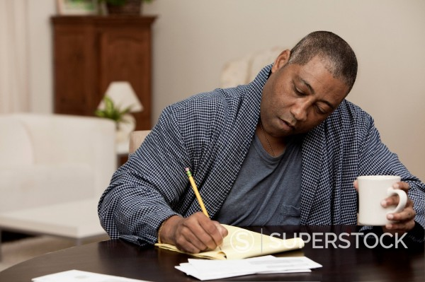 Stock Photo: 1589R-171275 Black man drinking coffee and writing on notepad