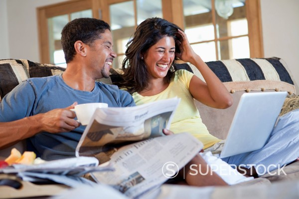 Laughing couple relaxing on sofa together : Stock Photo