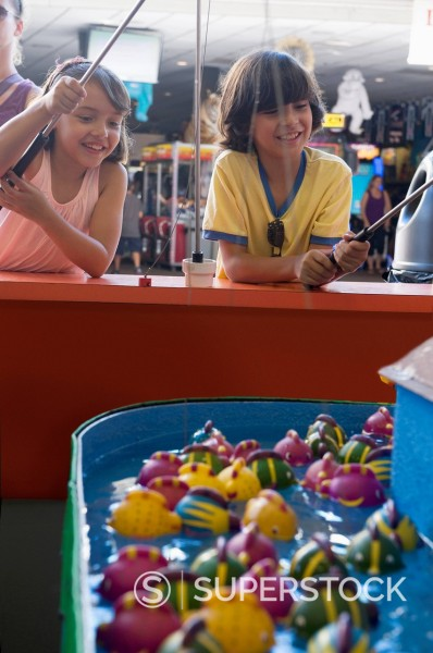 Stock Photo: 1589R-171286 Children playing arcade game in amusement park