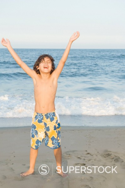 Happy boy cheering on beach : Stock Photo