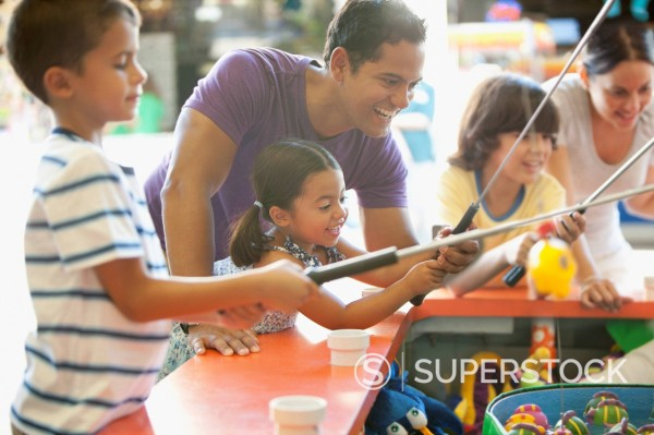 Hispanic family playing arcade game in amusement park : Stock Photo
