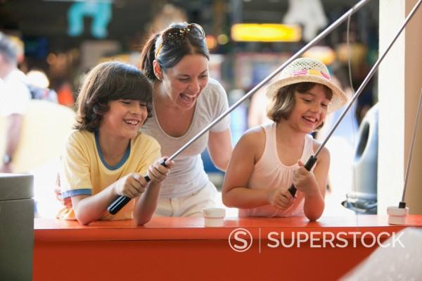 Hispanic family playing arcade game in amusement park : Stock Photo
