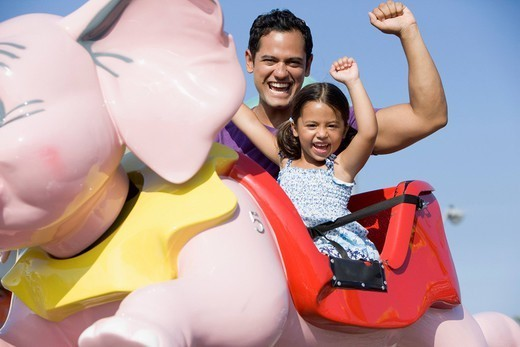Hispanic father and daughter riding amusement park ride : Stock Photo