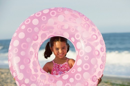 Smiling girl holding inflatable ring on beach : Stock Photo