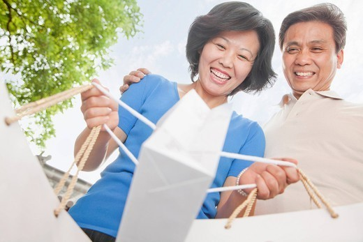 Stock Photo: 1589R-171345 Older Chinese couple carrying shopping bags