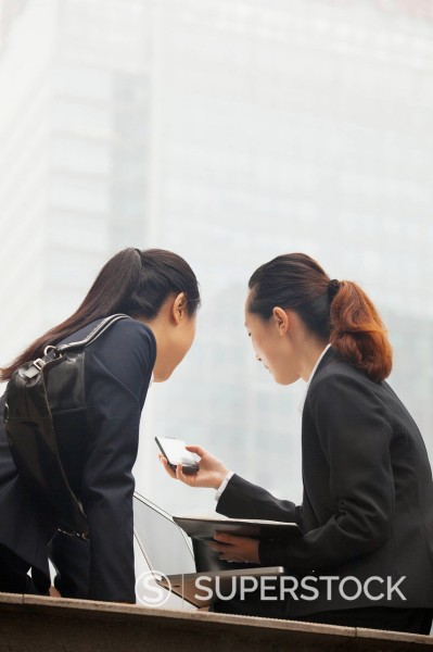 Chinese businesswomen using cell phone : Stock Photo