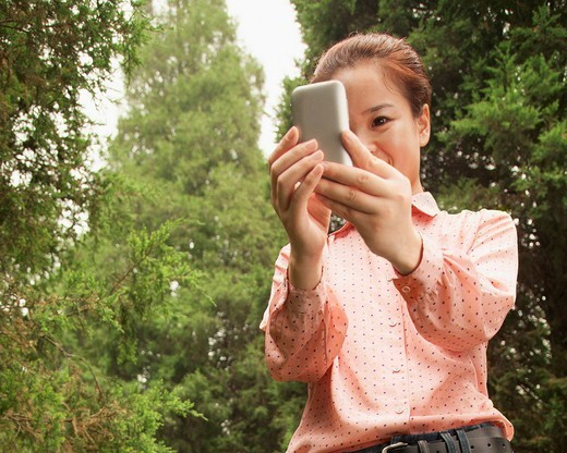Chinese woman using cell phone : Stock Photo