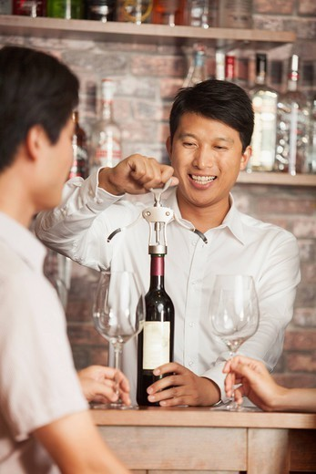 Chinese bartender uncorking bottle of wine : Stock Photo