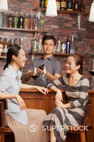 Stock Photo: 1589R-171398 Chinese bartender pouring glasses of wine