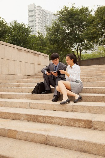 Chinese business people reading planner : Stock Photo