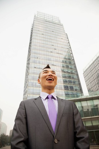 Chinese businessman smiling outdoors : Stock Photo