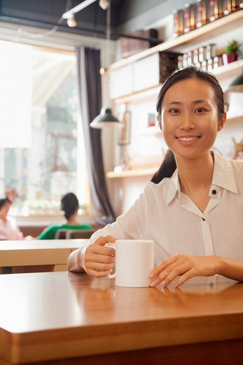 Chinese woman having coffee in cafe : Stock Photo