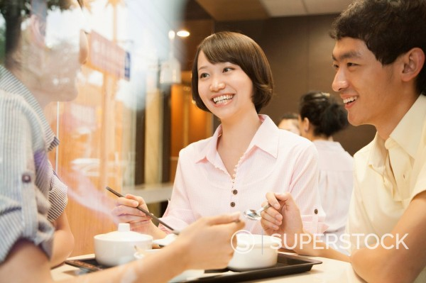 Chinese friends eating together in cafe : Stock Photo