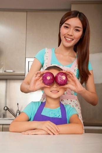 Chinese woman holding onions over daughter´s eyes : Stock Photo