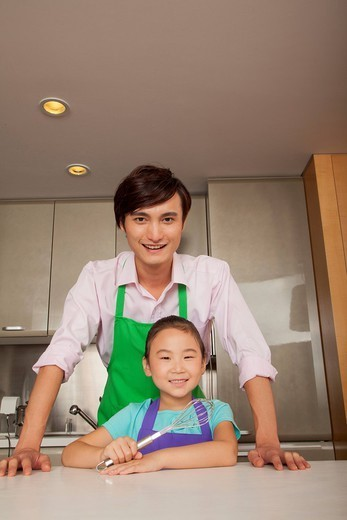 Chinese father and daughter standing in kitchen : Stock Photo
