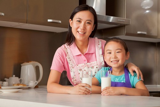 Chinese mother and daughter drinking milk : Stock Photo