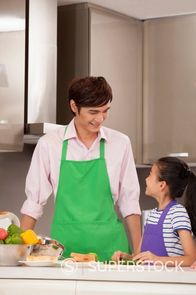 Stock Photo: 1589R-171478 Chinese father and daughter cooking in kitchen