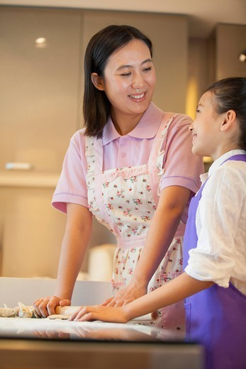 Chinese mother and daughter baking together in kitchen : Stock Photo