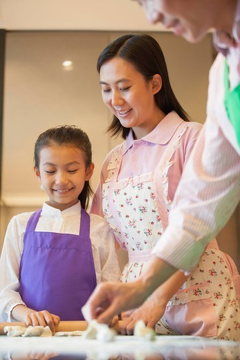 Chinese family baking together in kitchen : Stock Photo
