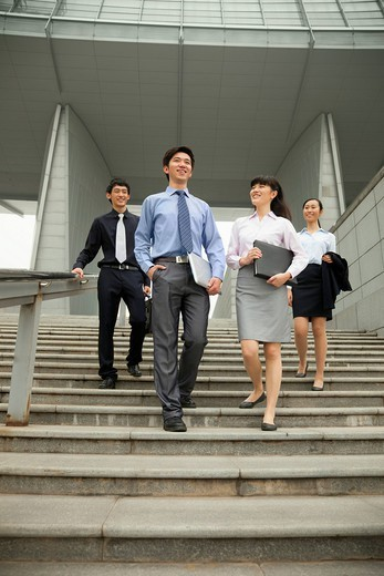 Chinese business people talking on city steps : Stock Photo