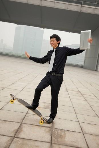 Chinese businessman doing tricks on skateboard : Stock Photo