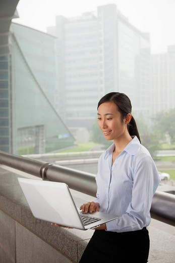 Chinese businesswoman using laptop outdoors : Stock Photo
