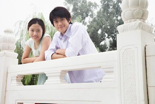 Chinese couple leaning on railing : Stock Photo