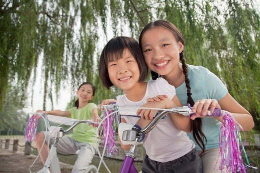 Chinese girls riding bicycles in park : Stock Photo