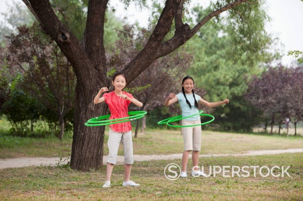 Chinese girls playing with hula hoops in park : Stock Photo