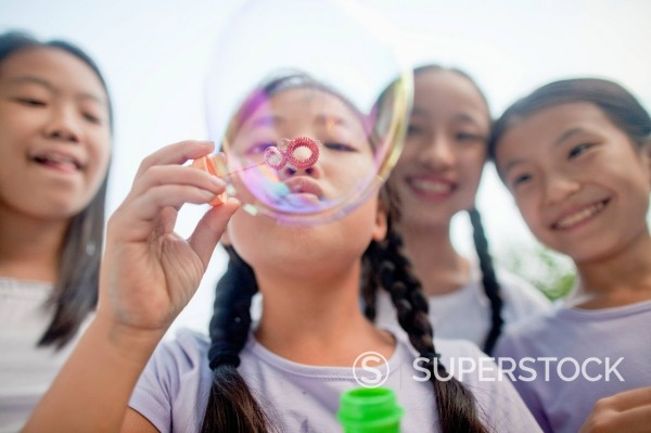 Stock Photo: 1589R-171689 Chinese girls blowing bubbles in park