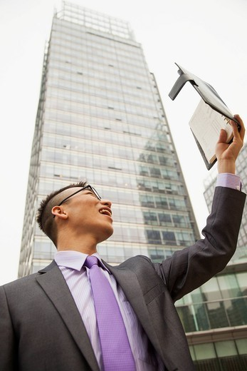 Chinese businessman reading planner outdoors : Stock Photo