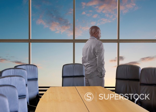 African American businessman looking out office window : Stock Photo