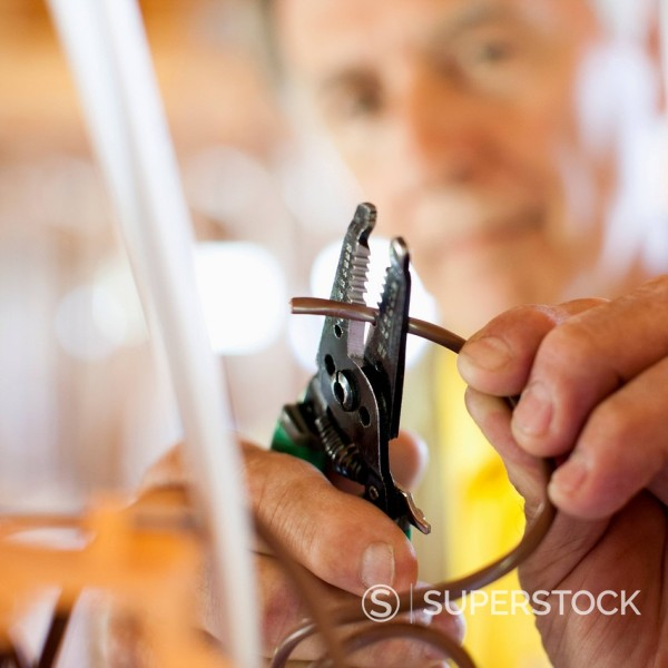 Stock Photo: 1589R-171734 Close up of Caucasian man snipping wire