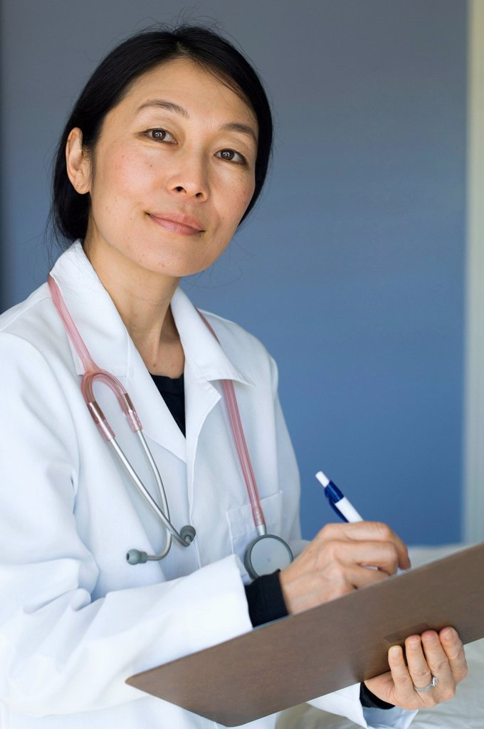 Japanese doctor writing on clipboard : Stock Photo