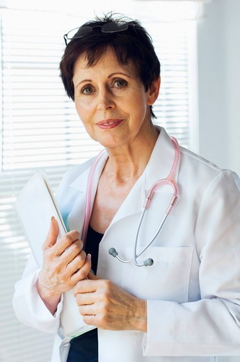 Stock Photo: 1589R-171764 Caucasian doctor holding clipboard in office