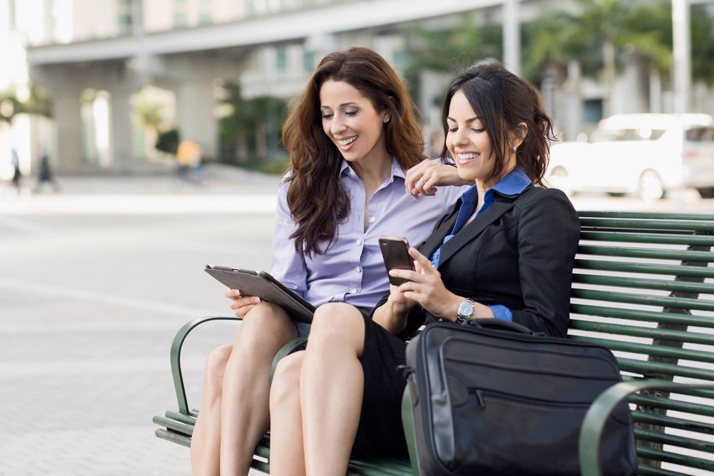 Stock Photo: 1589R-171774 Hispanic businesswomen on bench using cell phone and digital tablet