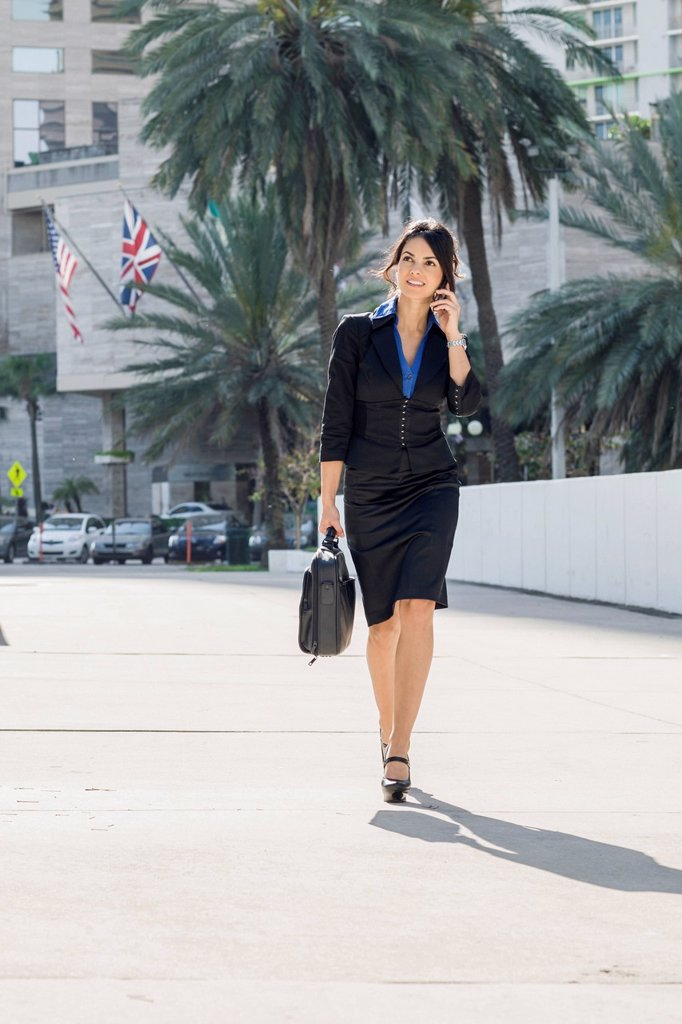 Stock Photo: 1589R-171776 Hispanic businesswoman walking and talking on cell phone