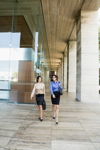 Hispanic businesswomen walking together : Stock Photo