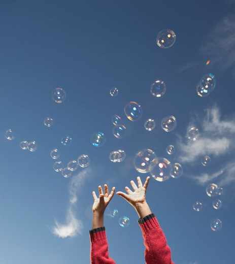 Stock Photo: 1589R-17182 Young girl reaching for airborne bubbles