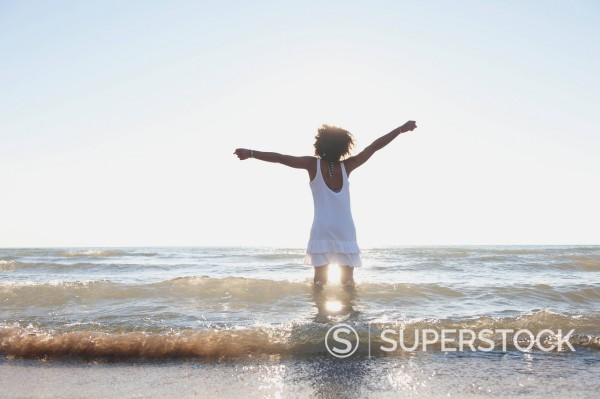 Black girl playing in waves on beach : Stock Photo