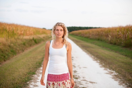 Caucasian woman standing on dirt road : Stock Photo