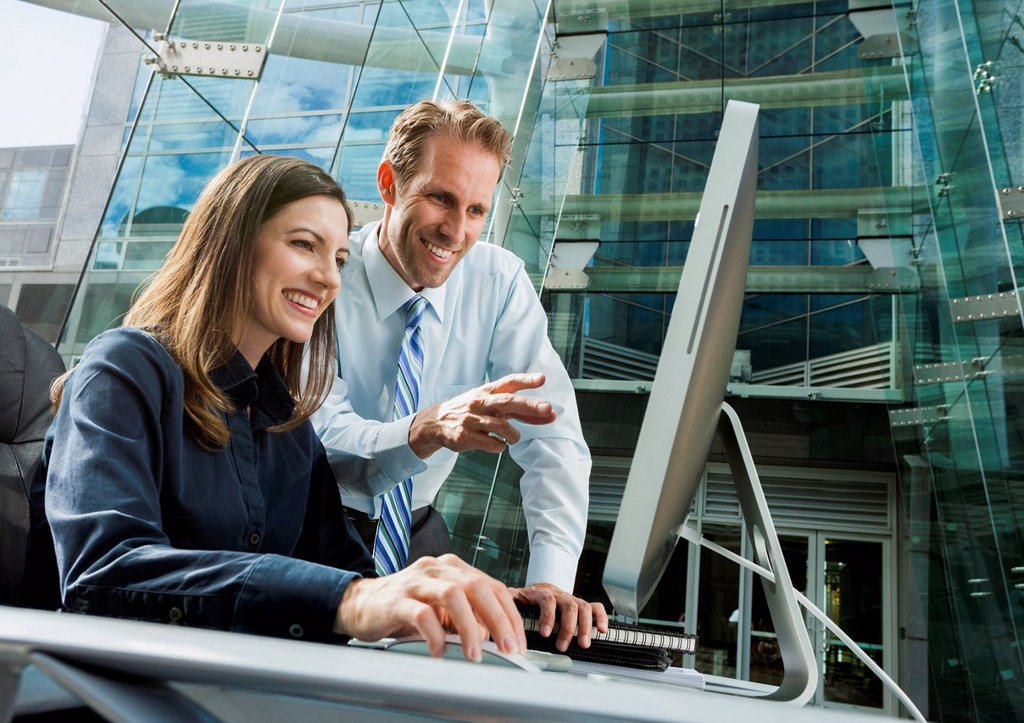 Caucasian business people working at computer : Stock Photo