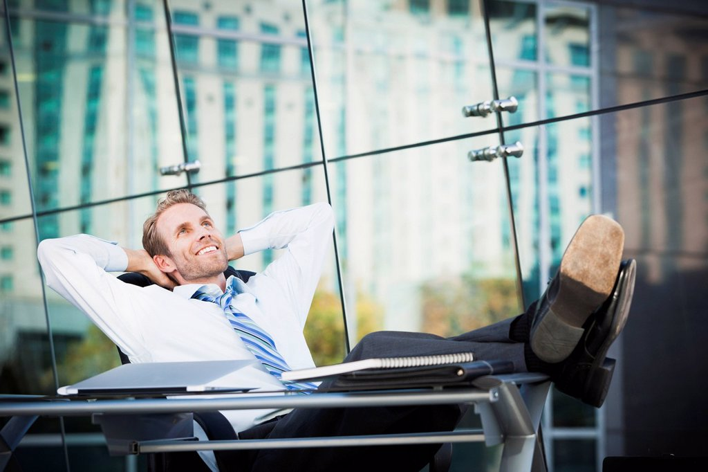Stock Photo: 1589R-171903 Caucasian businessman relaxing at desk