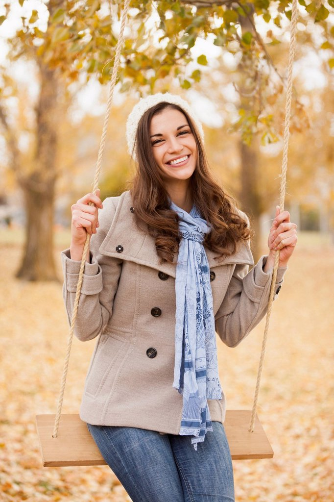 Stock Photo: 1589R-171931 Caucasian woman sitting on swing in autumn leaves