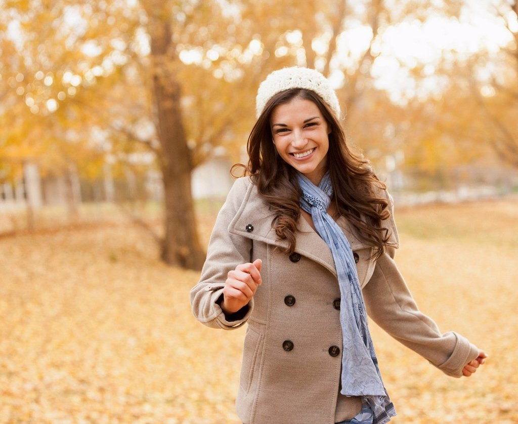 Caucasian woman walking in autumn leaves : Stock Photo