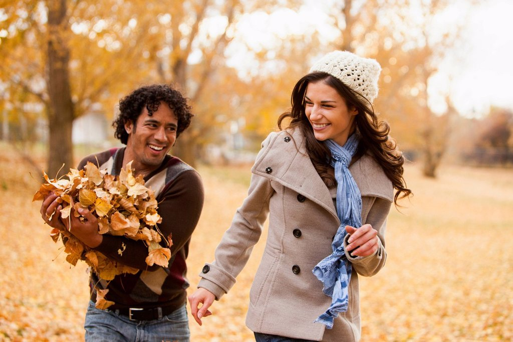 Couple playing in autumn leaves : Stock Photo