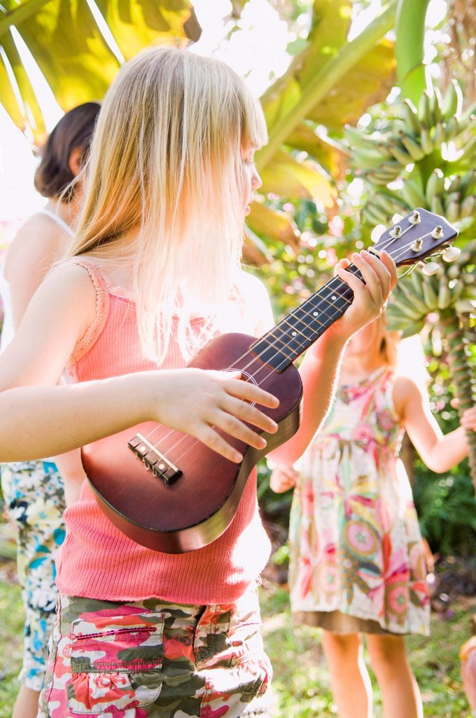 Stock Photo: 1589R-171973 Caucasian girl playing ukulele outdoors