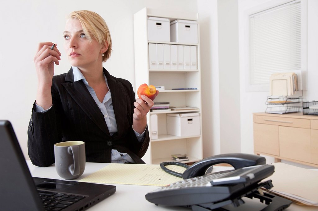 Caucasian businesswoman eating at desk in office : Stock Photo