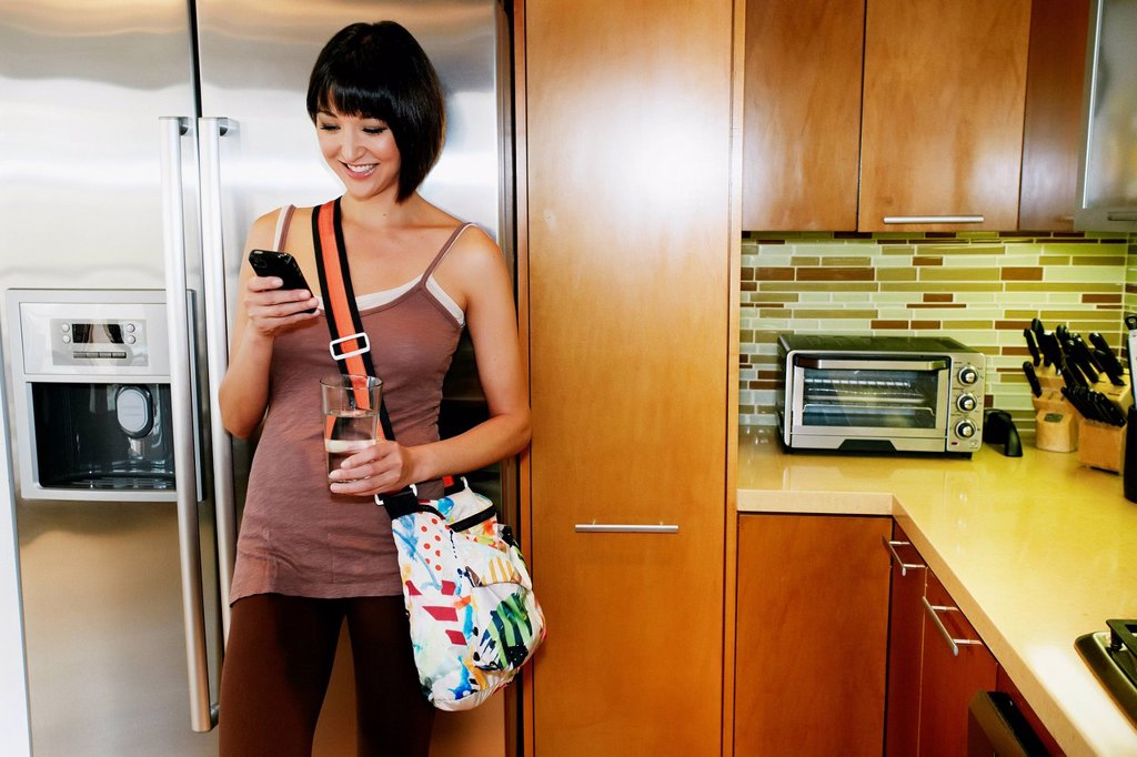 Stock Photo: 1589R-172084 Mixed race woman using cell phone in kitchen