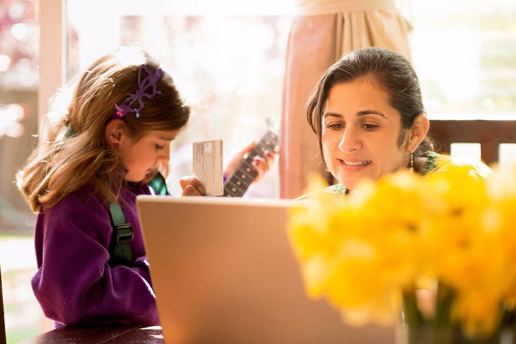Mother shopping online with daughter : Stock Photo